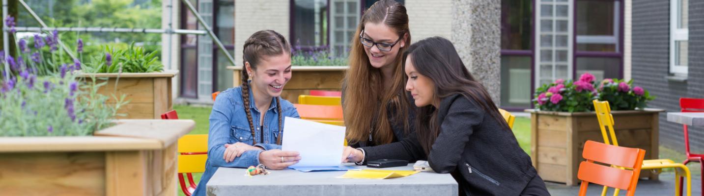 Drie studenten in overleg aan tafel in de buitenlucht