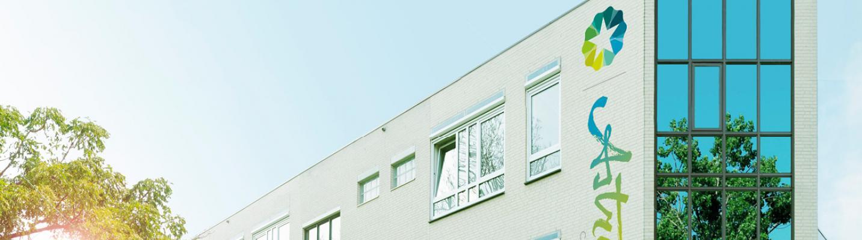 Het gebouw aan de Gruttostraat 10 met aan de zijkant het logo van Astrum College. In de reflectie van de ramen is een groene boom te zien en een stralende blauwe hemel.