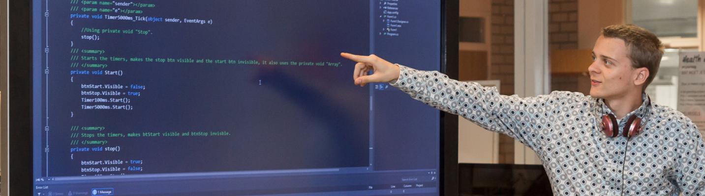 Student wijst een stuk code aan op een smartboard.