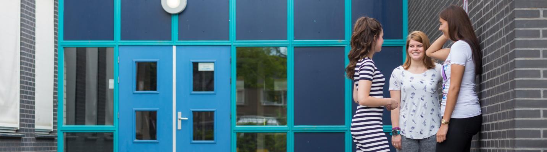 Drie vrouwlijke studenten met elkaar in gesprek bij de zij-ingang van Astrum College