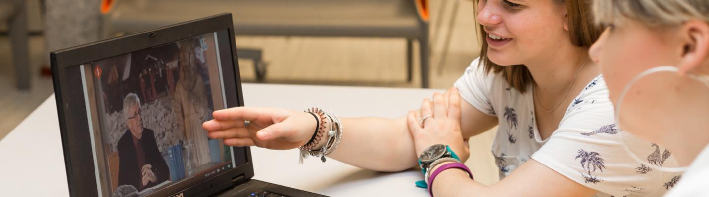 Een student geeft uitleg terwijl ze wijst naar een computerscherm waarop een video te zien is.