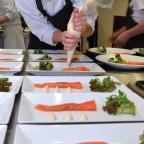Een kok die de laatste hand legt aan een gerecht met zalm.