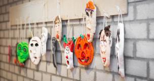 Maskers van aardewerk geschilderd in felle kleuren hangend aan een kapstok.